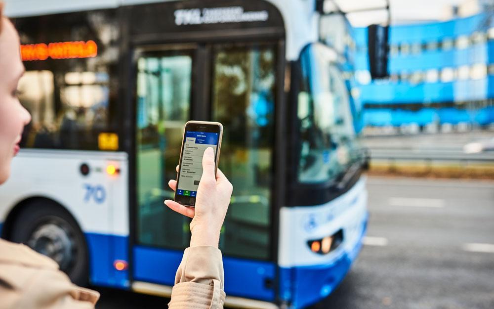 Kuvituskuva: Matkustaja tarkistaa mobiililippua bussin saapuessa pysäkille.