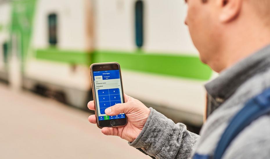 Tesoman seisake avataan 16.8. Mies juna-asemalla älypuhelin kädessään.